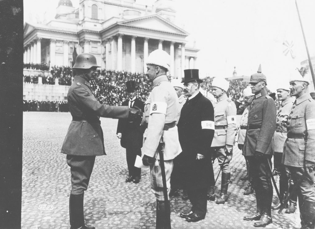 General Mannerheim is saluting a German officer at the Helsinki Senate Square after the Victory Parade of the White Army. In the photo you can also see the General of the German forces Rüdiger von der Goltz.