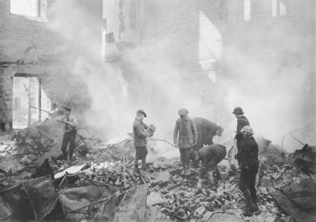 The occupation of Helsinki 1918. The Turku Barracks, Läntinen Heikinkatu 28 at the place of today's Lasipalatsi (Glass Palace), after the fire caused by the bombing carried out by the German forces. City inhabitants looking for canned food among the ruins.